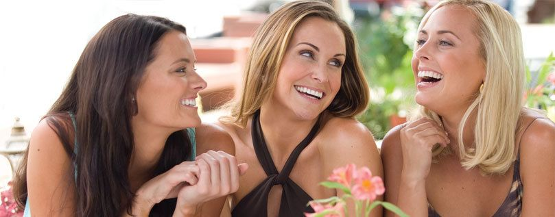 Invisalign®: a head and shoulders shot of three women smiling as they sit at a table.