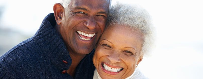 Inlays and onlays: a head and shoulders image of an older man and woman smiling into the camera.