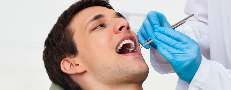 Root Canal: an image of a man's head as a dentist prepares to examine his teeth.