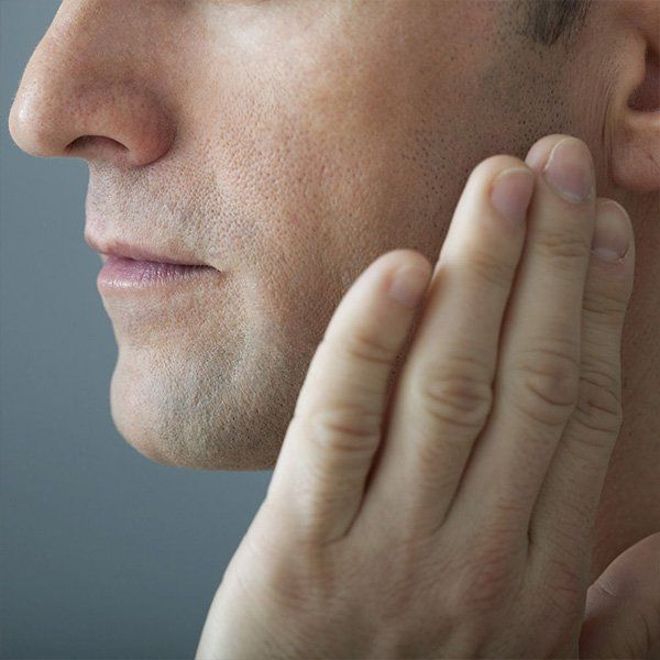 Photo of man with hand on jaw in pain