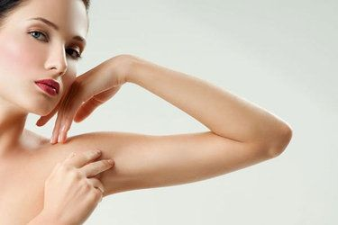 A woman pinches the excess fat in her upper arm
