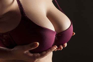 A woman in a maroon bra hols up her breasts