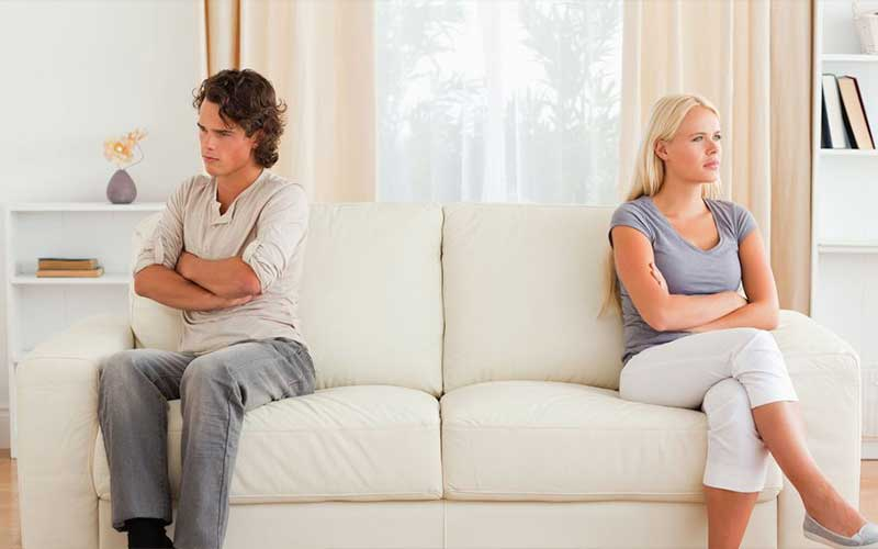 Photo of a couple on opposite ends of a couch
