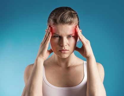 Woman holding her head due to painful migraine headaches.