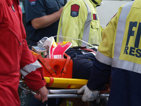 A cyclist on a stretcher being put in an ambulance