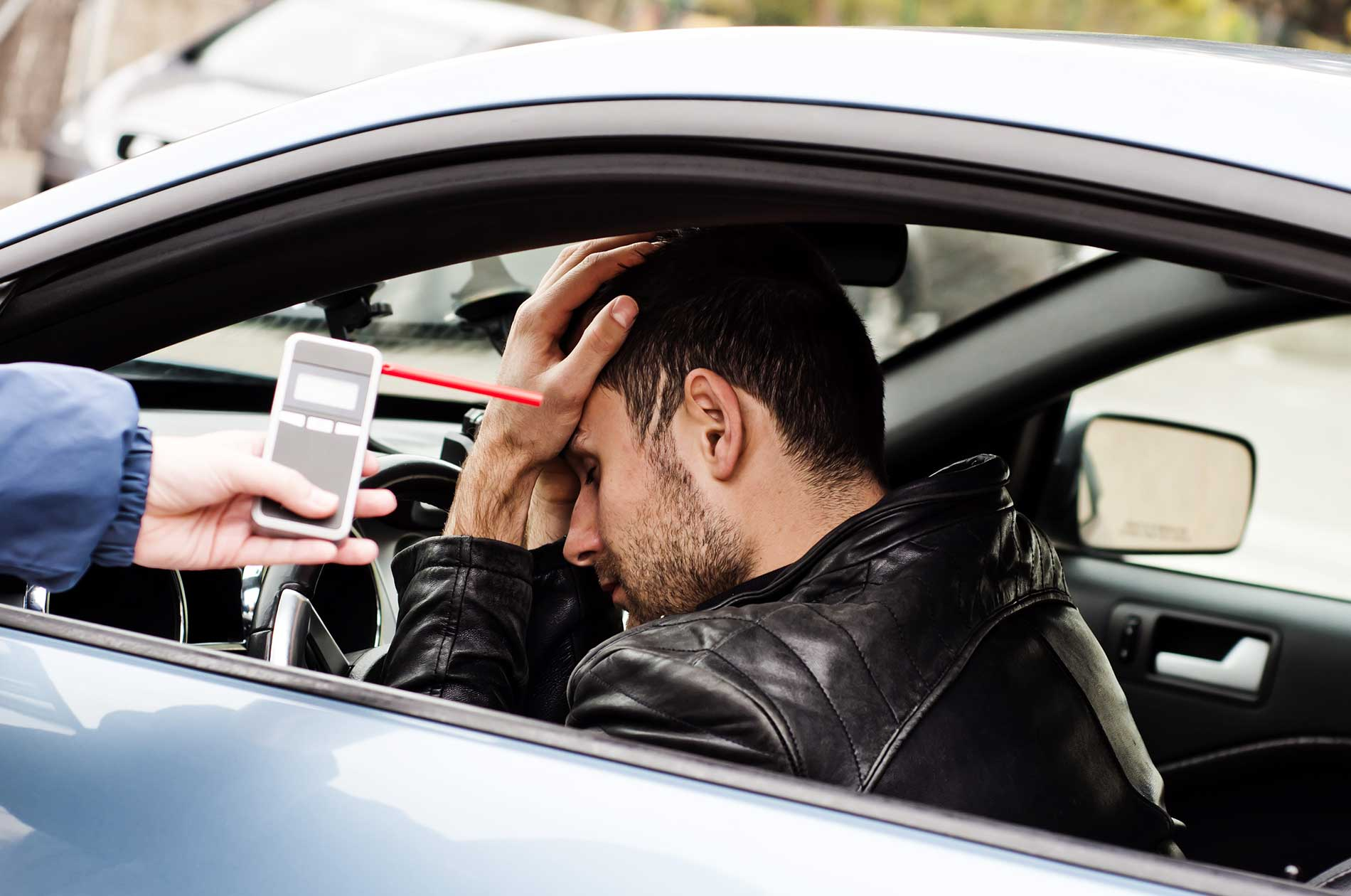 A man in a car refusing to take a breathalyzer test
