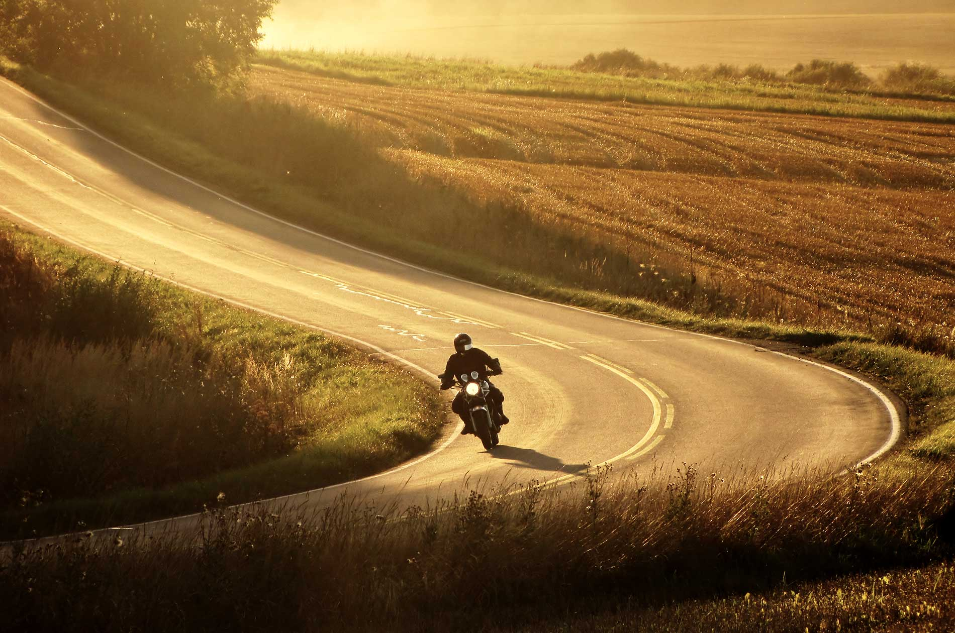 A motorcycle rider on a country road