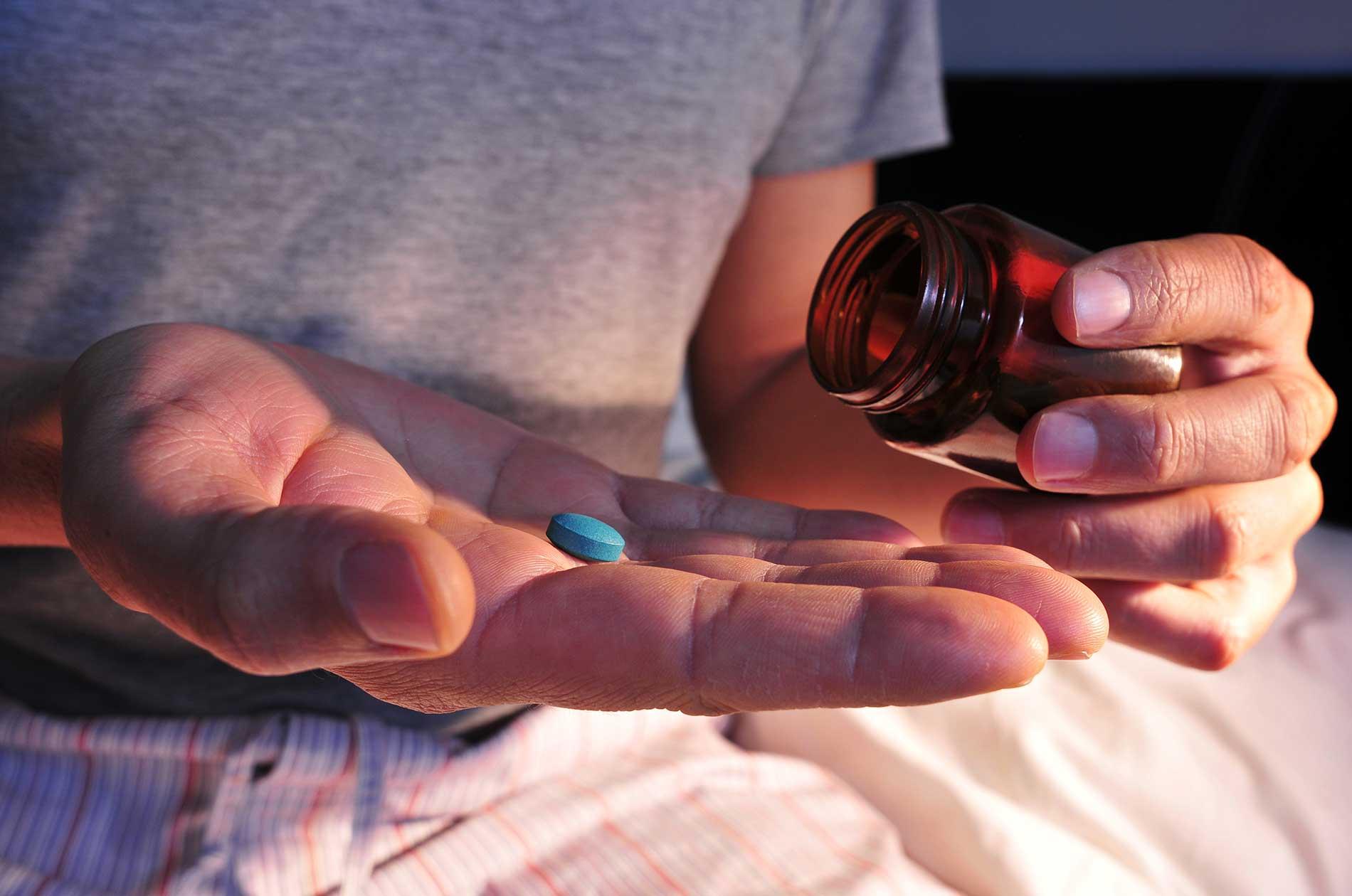 A man holding a viagra pill