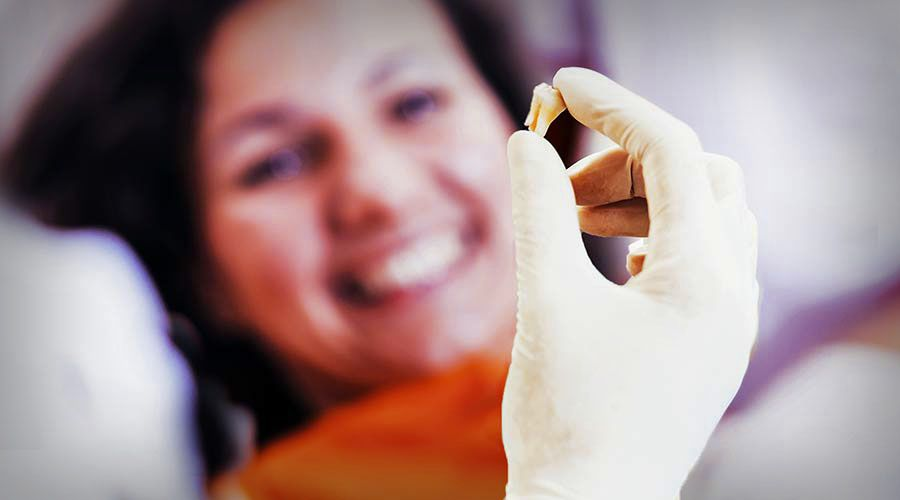 A dentist holds up a tooth in his hand while a woman smiles in the background