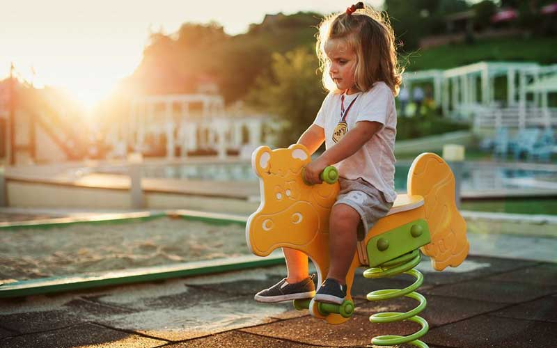 Young girl riding rocking horse on playground