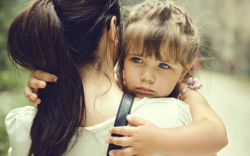 Woman holding young girl in her arms