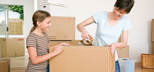 Mother and daughter packing moving boxes