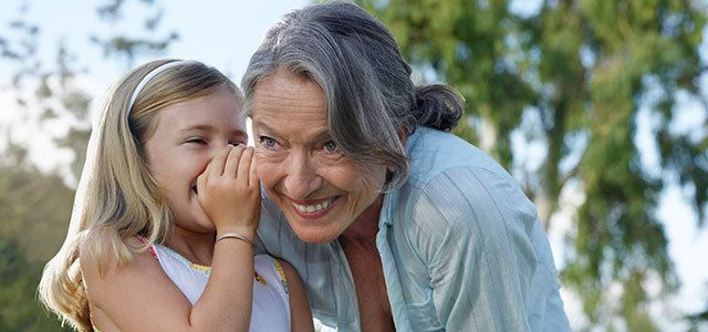 Young girl whispering in grandmother's ear