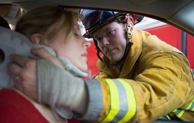 Photo of firefighter treating a woman in a car accident