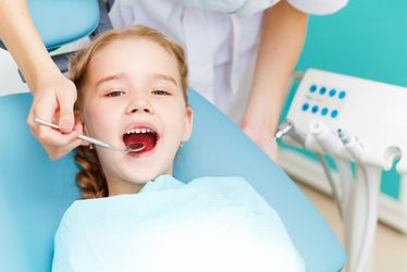 Nurse with dental tool looking in the mouth of child in dental chair.