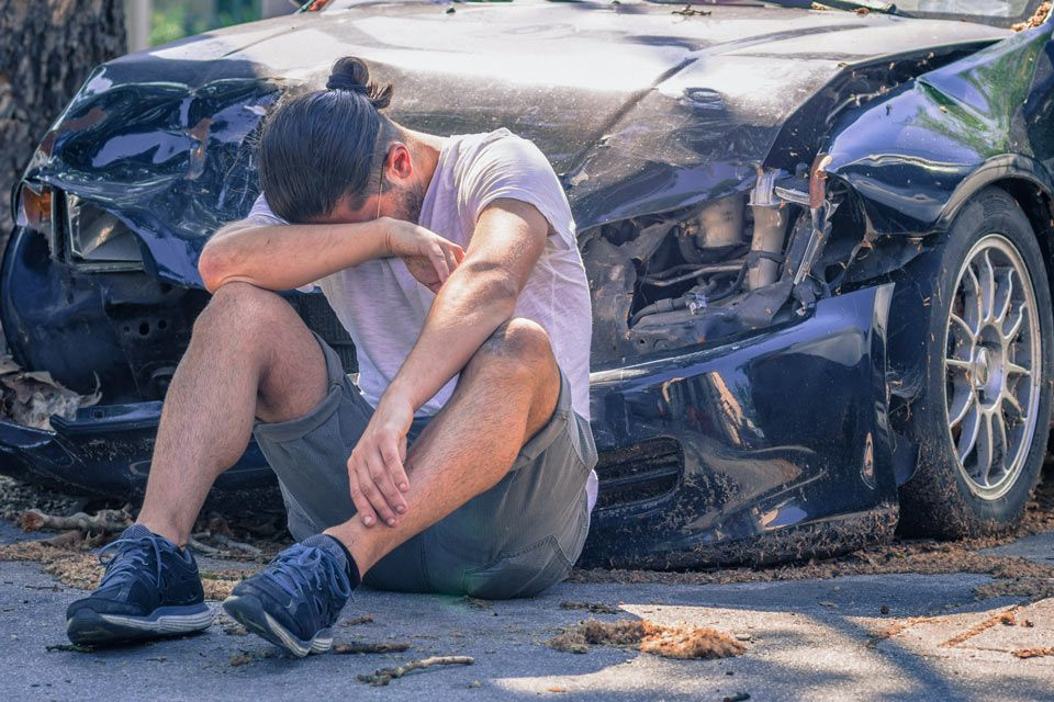 Upset man sitting in front of wrecked car