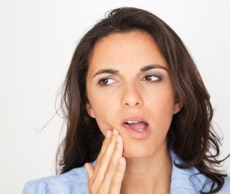 Photo of woman holding jaw in pain