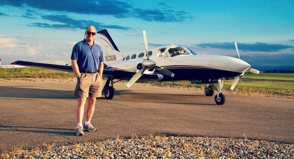 Dr. Stephen Brown in front of his airplane.
