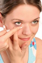 A woman inserting her contact lenses.