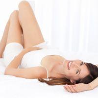 Una hermosa joven acostada de espaldas con las rodillas dobladas, mirando por encima del hombro.