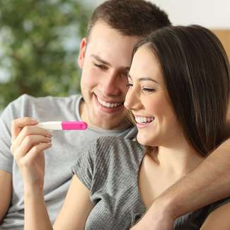 A smiling couple looks at a pregnancy test