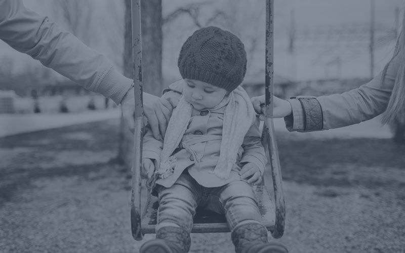 A young child on a swing in between her parents.