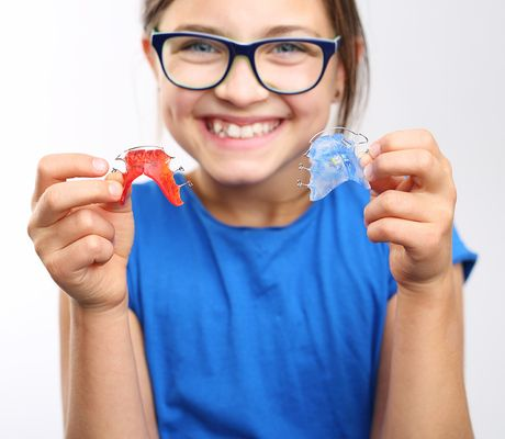 Smiling girl holding retainers