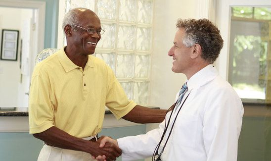 Dr. Burden shaking hands with a patient in a yellow shirt