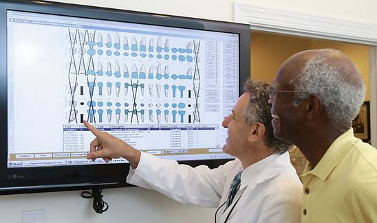 Dr. Burden stands with a patient and points to a screen
