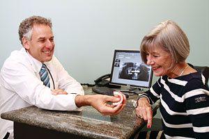 Dr. Burden showing a patient a model of teeth