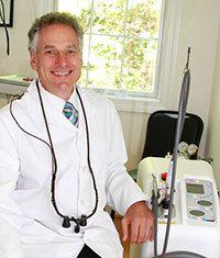 Dr. Burden sitting next to the dental laser