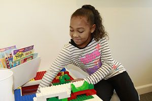 A girl in a striped shirt plays with a Lego® table