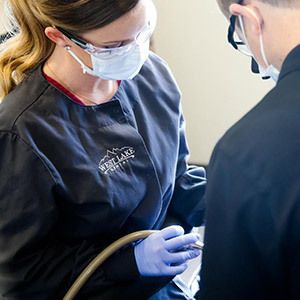 A hygienist and Dr. Andy Maples clean a patient's teeth