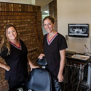Two female hygienists stand next to a dental chair