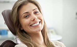 Happy smiling woman in dental chair