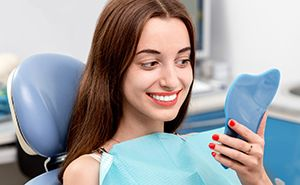 Woman in dental chair examining smile in mirror