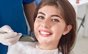 Happy young woman in dental treatment room