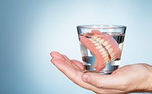 Hand holding dentures inside glass of water