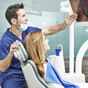 Dentist and patient looking at x-rays on computer monitor
