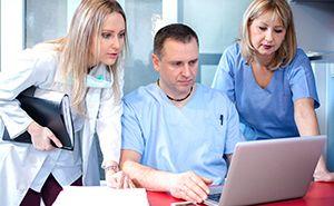 Dental team examining patient chart on laptop