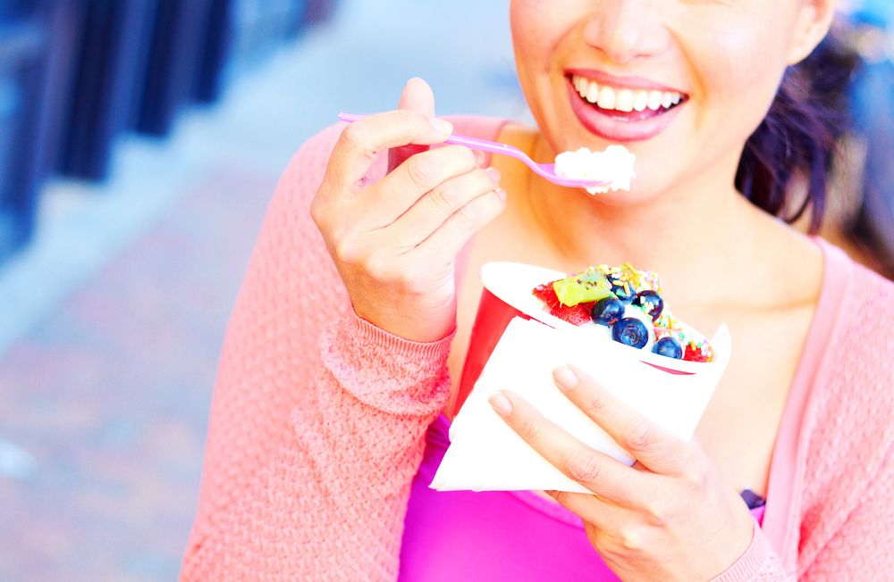 Close up of woman walking on sidewalk while eating frozen yogurt with berries
