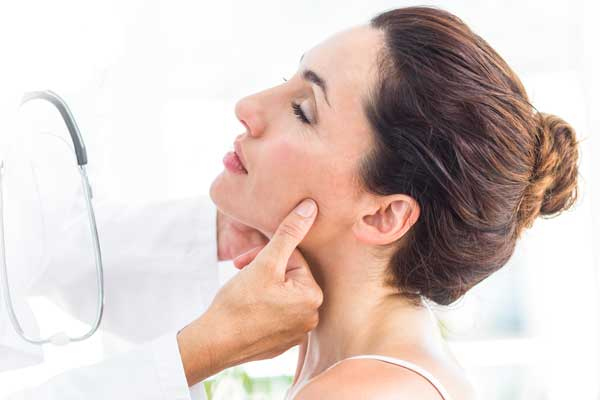 Doctor examining woman's jaw