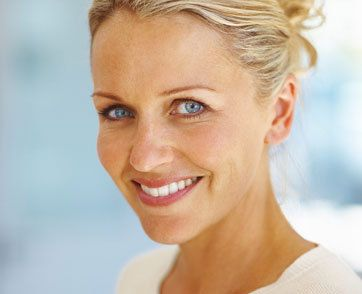 A smiling woman with blonde hair and blue eyes.