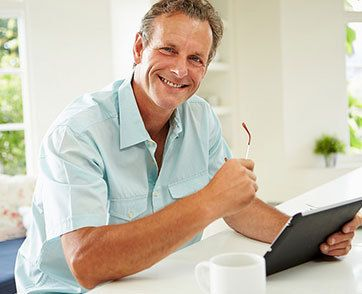 A smiling man in a bright shirt holding a tablet and glasses.