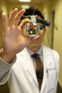 A doctor holding a vision care imaging tool.
