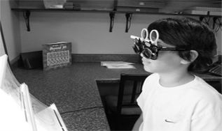 A young boy undergoing vision therapy treatment for binocular vision evaluation.