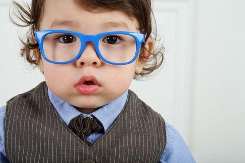 A toddler wearing blue eyeglasses.