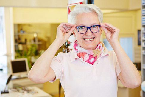 A smiling older woman wearing eyeglasses.