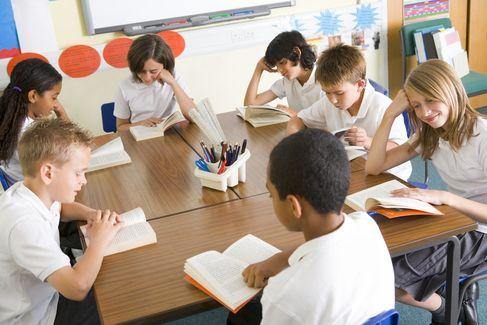 A group of children sitting around school desks.