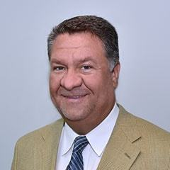 Dr. Chadwick J. Harris wearing a mustard suit.